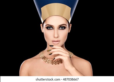 Beauty shot in Egyptian style. Beautiful adult girl in Nefertiti. Luxury and wealth. Golden decoration. Makeup, rough look. Black background. Manicure nail mosaic, hand near the face