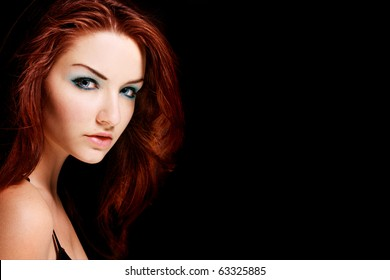 A beauty shot of a young blue eyed woman with her red hair looking at the camera.