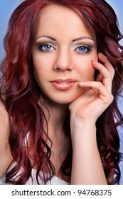 A beauty shot of a young blue eyed woman with red hair