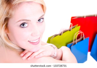 Beauty shot of a young gorgeous woman looking over her shoulder whit shopping bags in the ground