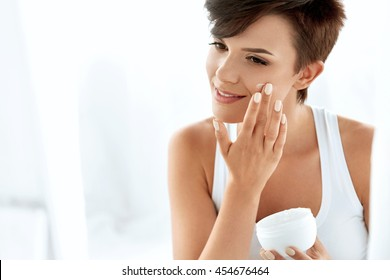 Beauty Skin Care. Beautiful Happy Woman Applying Cosmetic Cream On Clean Face. Closeup Portrait Of Healthy Smiling Female Model With Natural Makeup, Fresh Soft Pure Skin Applying Moisturizing Lotion