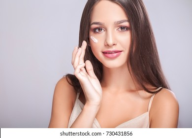 Beauty Skin Care. Closeup Of Beautiful Sexy Smiling Girl Putting Cream On Fresh Soft Pure Skin. Portrait Of Young Woman With Natural Makeup Applying Beauty Cosmetics Product On Cheek. High Resolution
