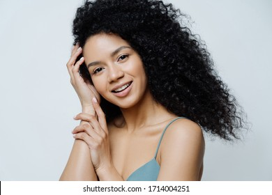 Beauty, skin care concept. Beautiful tender young woman with Afro hair has healthy well cared skin, touches hair, looks positively at camera, shows bare shoulders, isolated on white background.
