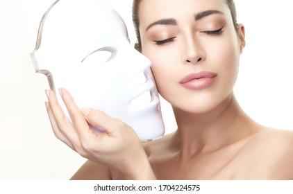 Beauty- und Hautpflegekonzept. Gesunde Hautmodellfrau mit Gesichtsmaske. Lichttherapie Behandlung der Haut Verjüngung durch Gesichtsmaske. Hautverjüngungstherapie. Einzeln auf Weiß mit Kopienraum