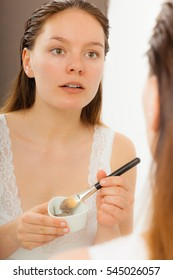 Beauty skin care cosmetics and health concept. Young woman applying facial mud clay mask to her face in bathroom