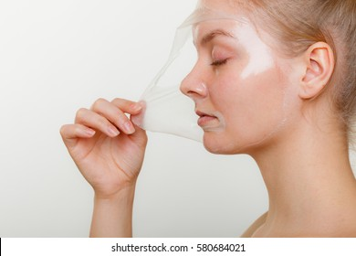 Beauty skin care cosmetics and health concept. Young woman face profile, girl removing facial peel off mask. Peeling.