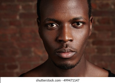 Beauty and skin care. Highly-detailed close up portrait of good-looking dark-skinned young man with clean healthy glowing skin, looking at camera with serious confident expression, posing in studio
