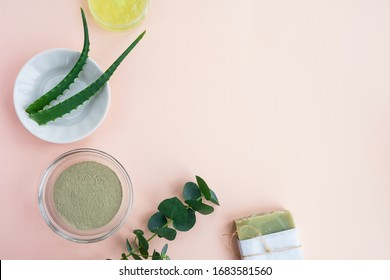 Beauty skin care ingredients. Bowl with clay, aloe, cream gel, handmade soap and eucalyptus leaves on pastel background. Natural organic cosmetics concept. Top view, flat lay, copy space