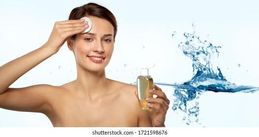 beauty, skin care and people concept - smiling young woman with toner or cleanser and cotton pad cleansing face over blue background with bubbles in water splash