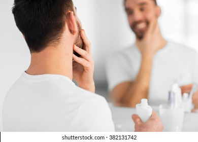 beauty, skin care and people concept - close up of smiling young man applying cream to face and looking to mirror at home bathroom