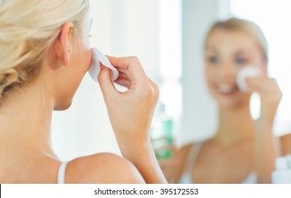 beauty, skin care and people concept - close up of smiling young woman cleaning her face with cotton disc and lotion at bathroom