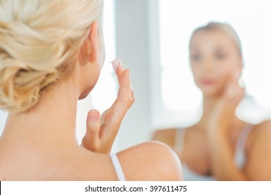 beauty, skin care and people concept - close up of young woman applying cream to face and looking to mirror at home bathroom