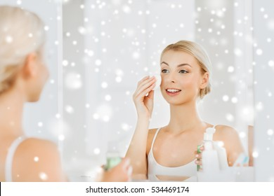 beauty, skin care and people concept - smiling young woman applying lotion to cotton disc for washing her face at bathroom over snow