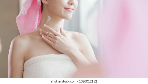 Beauty skin care woman look to mirror and apply neck cream after shower