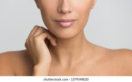 Beauty skin care. Woman with naked shoulders, grey background