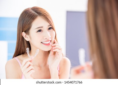 Beauty skin care woman touch her chin and use invisible braces in front of mirror
