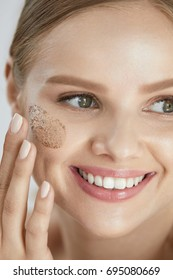 Beauty Skin Peeling. Closeup Smiling Female Applying Scrub On Face. High Resolution