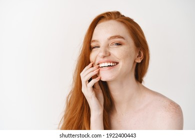 Beauty and skincare. Close-up of happy redhead woman with pale perfect skin, laughing and showing white teeth, standing naked on studio background.