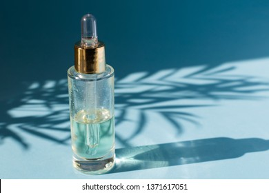 Beauty skincare concept template - dropper glass bottle with cosmetic oil or serum, natural hard light, deep shadows, light blue background, copy space
