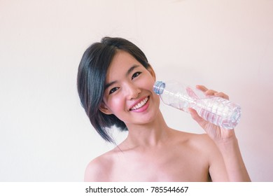 Beauty Skincare concept- Young Asian woman after shower  smiling holding a bottle of water