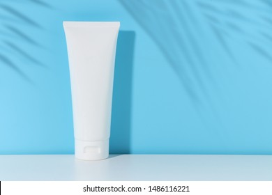 beauty skincare cosmetic mockup cream lotion bottle pakage on white background, sunscreen protection with summer coconut palm leaf tree shadow blue background