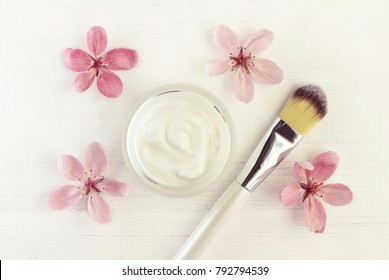 Beauty skincare cream in cosmetic jar, delicate fresh pink spring blossom, application brush, top view white wooden table.