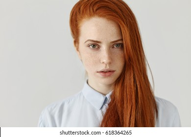 Beauty, skincare and haircare. Gorgeous young woman with perfect clean freckled skin s wearing her long ginger hair loose on side looking at camera keeping lips slightly parted, dressed in blue shirt