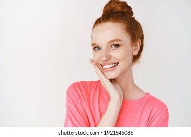 Beauty and skincare. Smiling girl with ginger hair combed in messy bun, touching perfect skin and smiling, standing without makeup on white background.