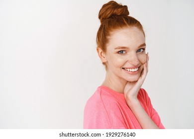 Beauty and skincare. Smiling girl with ginger hair combed in messy bun, touching perfect and glowing skin and smiling, showing face without makeup, white background.