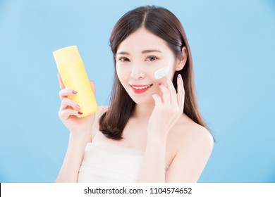 beauty skincare woman take sun protection cream on the blue backgorund