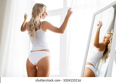 beauty, slimming and people concept - beautiful young woman in white underwear at mirror near window in morning at home