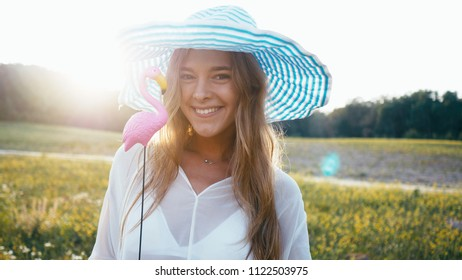 Beauty Smiling Girl on the Spring Field. Meadow. Portrait of Laughing And Happy young model woman with healthy long blowing hair Enjoying Nature. Beautiful Young Woman Outdoors in Slow Motion