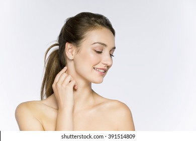 Beauty smiling girl portrait . Beautiful woman face. Isolated on a white background. Pretty Girl Touching her neck