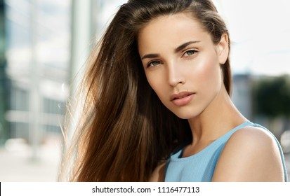 Beauty smiling happy model with natural make up and long eyelashes smiles outdoor. Copyspace. Young pretty student woman in the openspace.