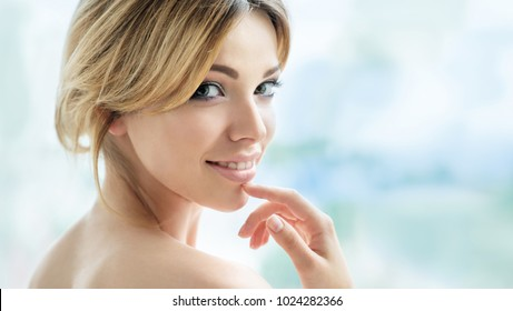 Beauty smiling model with makeup and long eyelashes posing front of the window. Spa and wellness, youth and  skincare concept. Make up, long hair and lashes. Close up, selective focus.
