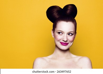 Beauty Smiling Teenager Model Girl. Beautiful Joyful teen girl with freckles, funny hairstyle and bright makeup. Isolated on a yellow background