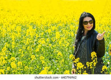 Beauty smiling woman giving thumb up in field
