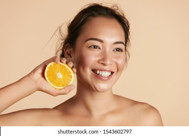 Beauty. Smiling woman with radiant face skin and orange portrait. Beautiful smiling asian girl model with natural makeup, healthy smile and glowing hydrated facial skin. Vitamin C cosmetics concept - Shutterstock ID 1543602797