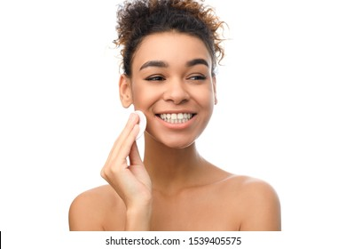 Beauty and spa. Black girl cleaning her face with cotton sponge, white background