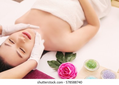 beauty and spa concept - happy woman in spa salon lying on the massage desk.