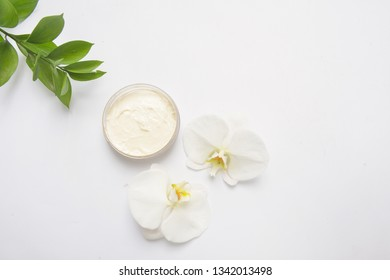 Beauty Spa concept. Opened plastic container with cream and White Phalaenopsis orchid flowers on white background