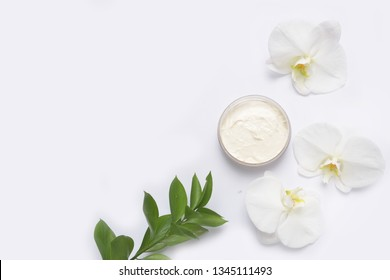 Beauty Spa concept. Opened plastic container with cream and White Phalaenopsis orchid flowers ,green leaves on white background