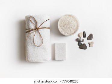 Beauty and spa concept. Towel, sea salt, pumice and stones on white paper background. Flat lay.