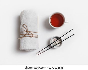 Beauty spa concept. Towel, tea cup and incense for spa treatments on white paper background. Flat lay.