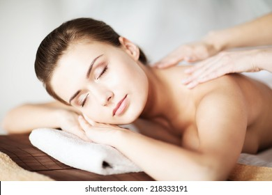 beauty and spa concept - woman in spa salon getting massage