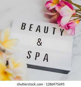 beauty and spa lightbox text surrounded by tropical frangipani monoi flowers