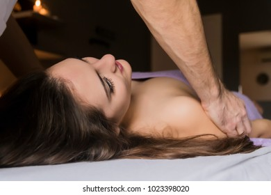 beauty, spa, resort and relaxation concept - beautiful woman in spa salon getting massage. Woman enjoying revitalizing shoulder and neck massage in spa. Unrecognizable physical therapist.