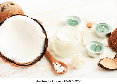 Beauty spa treatment with coconut oil, nuts and shredded coconut flakes for skin & body care, aroma relaxing tealight candles, cosmetic ingredients white table, pastel color.