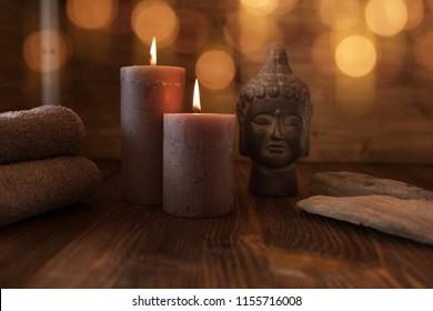 Beauty spa treatment with head of buddha statue and candles for a wellness concept