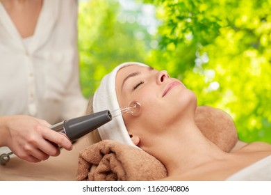 beauty, spa and wellness concept - woman having needle free mesotherapy or hydradermie facial treatment by microcurrent firming device over green natural background